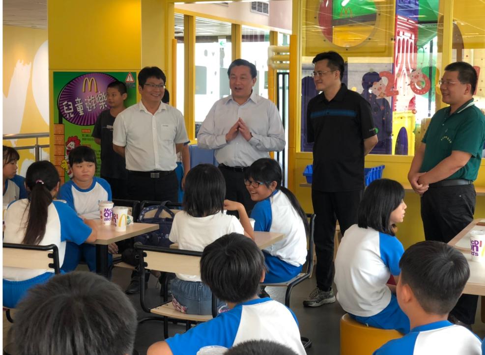 王定宇(站立者右三)沒忘記先前與新光國小學童約定,今天請師生吃麥當勞午餐。記者周...