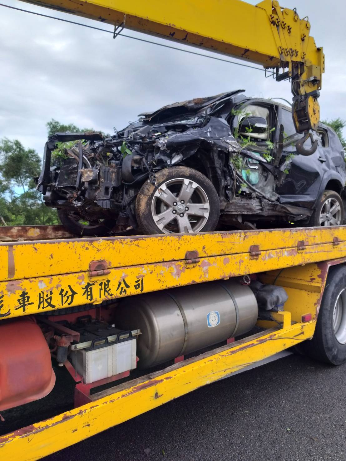 一輛廂型車疑失控衝撞護欄,整輛車翻落10多公尺深的邊坡,車輛毀損嚴重。記者余采瀅...