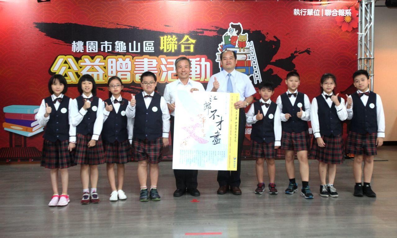 桃園市教育局聘任督學童政憲(圖中左)贈書給學校。記者葉英豪/攝影