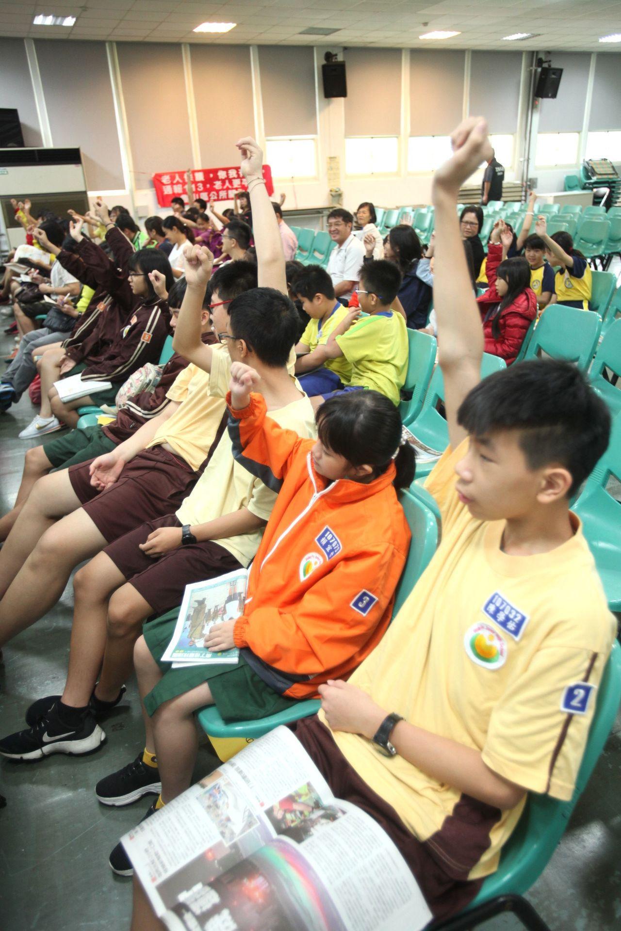 參與贈書各校孩子們,爭相搶著舉手表達近來都有閱讀課外讀物,獲得嘉評。記者葉英豪/...