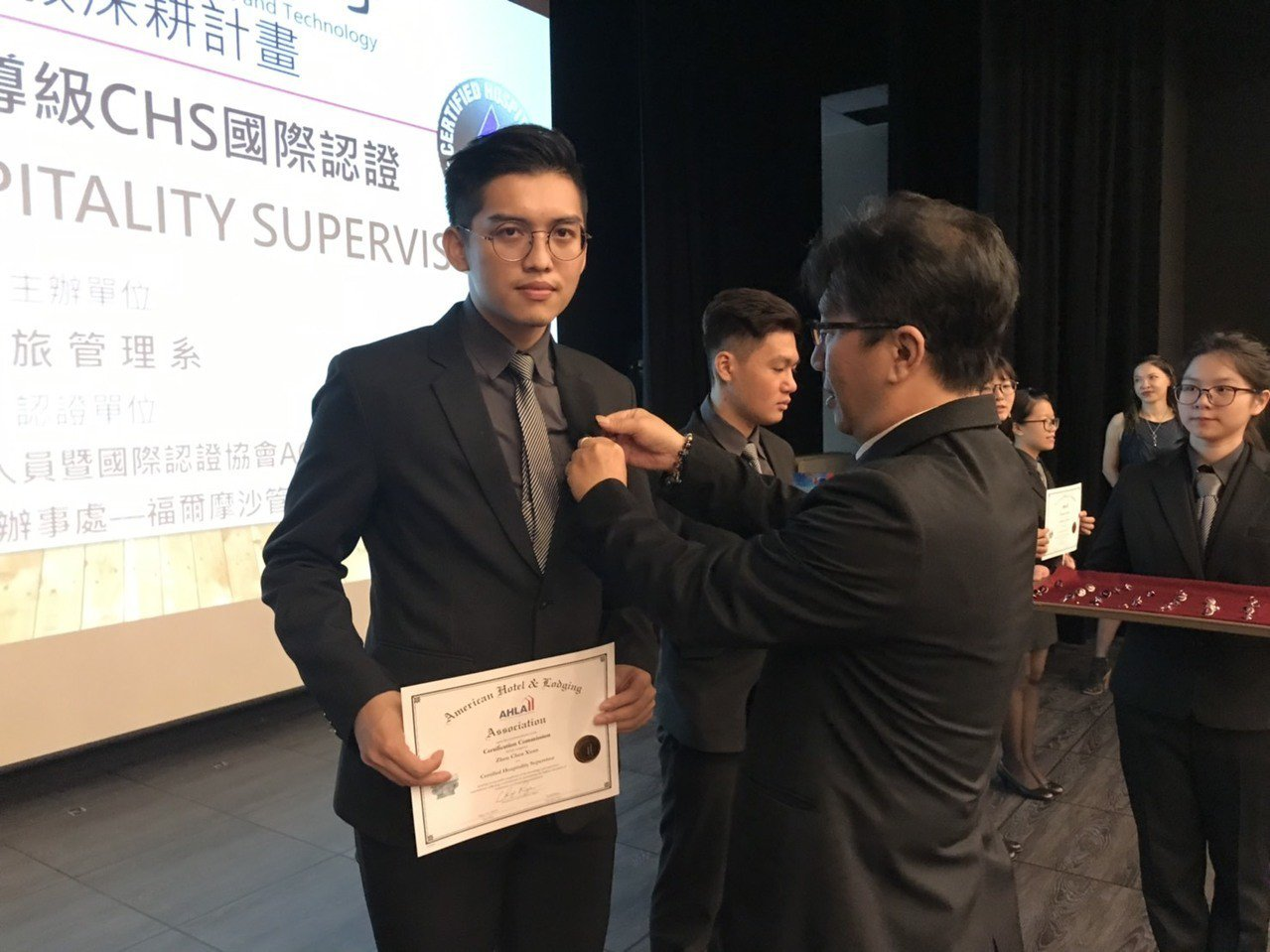 余紹君理事長(右)為通過認證許志鴻同學授證和別上勳章。圖/健行科大提供