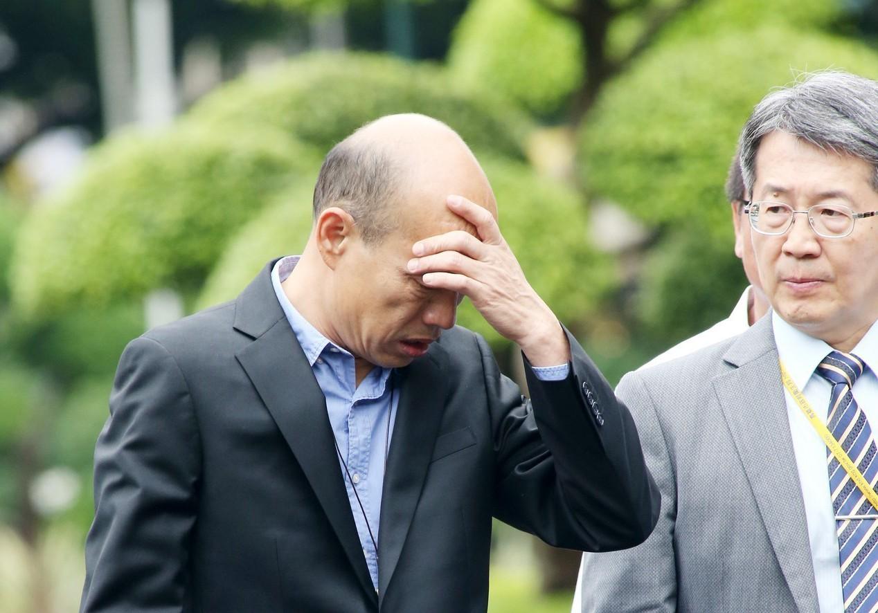 高雄市長韓國瑜(左)前天出席行政院會,會後他走出廣場受訪時,途中一度以手撫額。圖...