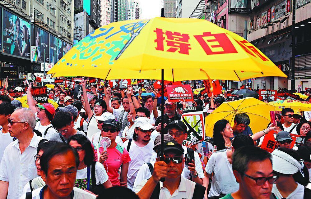 香港民陣日前發動「反送中」大遊行,有人持當年象徵佔領中環的黃傘。(路透)