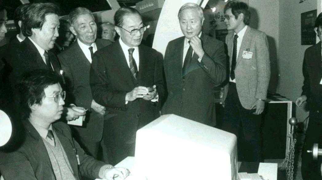 1986年12月,時任行政院長俞國華參觀資訊月展覽,聽取工研院長張忠謀(右三)解...