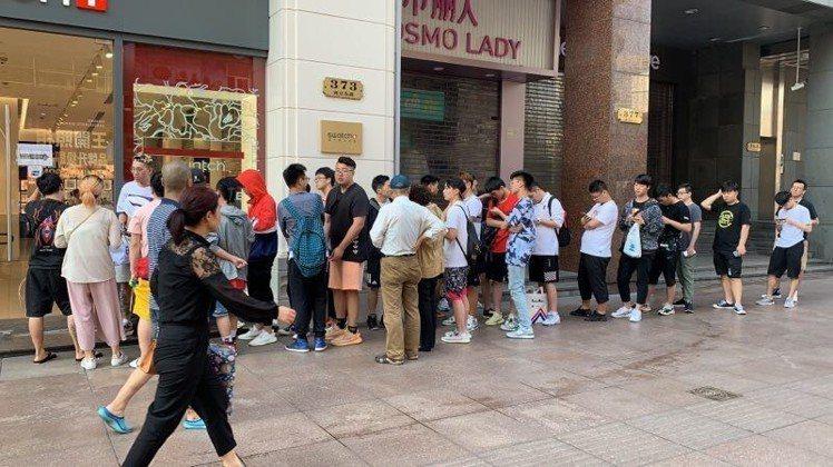 在中國的SWATCH形象店前,出現了要購買SWATCH和BAPE聯名表的人潮。圖...