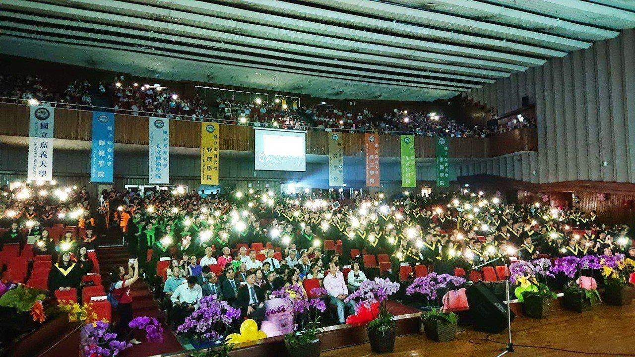 嘉大畢業典禮最後,全體畢業生以蘇打綠「當我們一起走過」合唱,會場點亮手機燈光隨音...