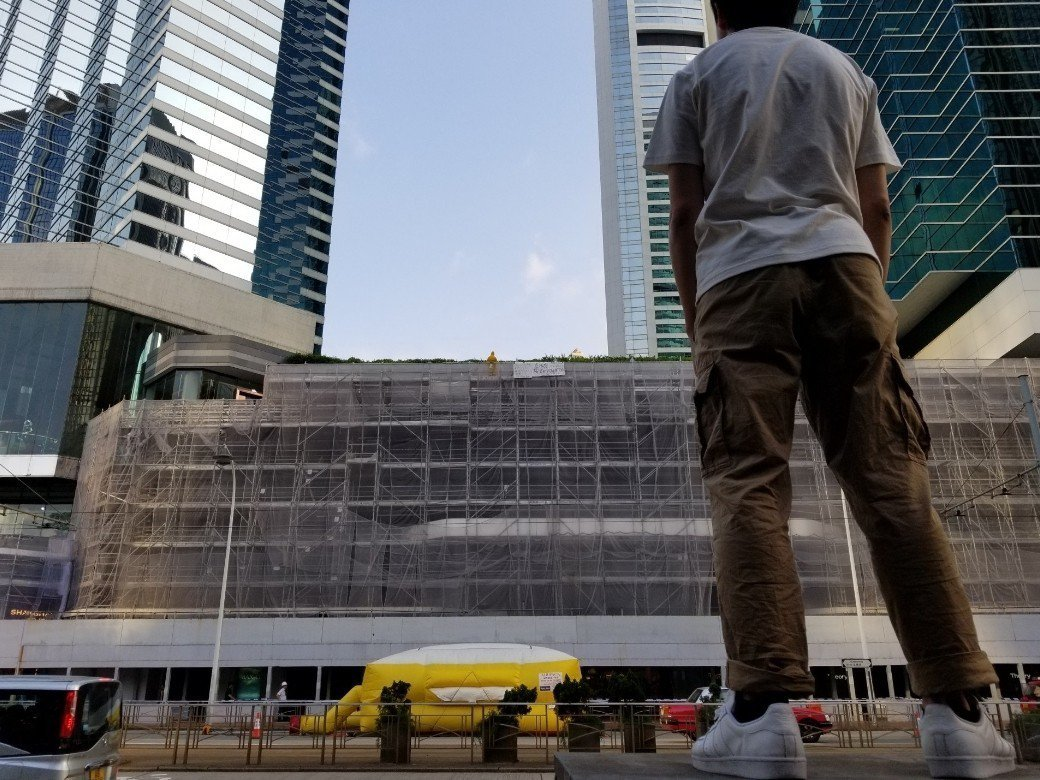 該名黃衣人危站超過一小時,立法會議員鄺俊宇到場,希望與對方對話。(香港01)