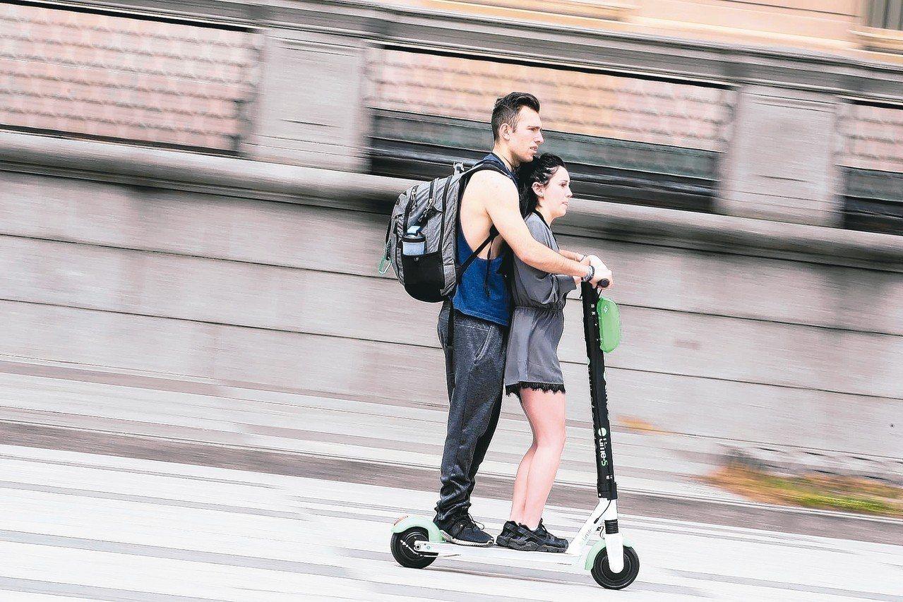 一對男女在華府白宮附近共乘電動滑板車。 路透