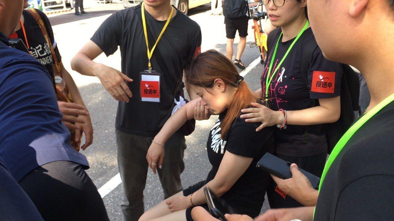 一名年約20歲的女子不耐酷暑,一度昏厥並被一旁民眾攙扶到陰涼處休息。記者李隆揆/...