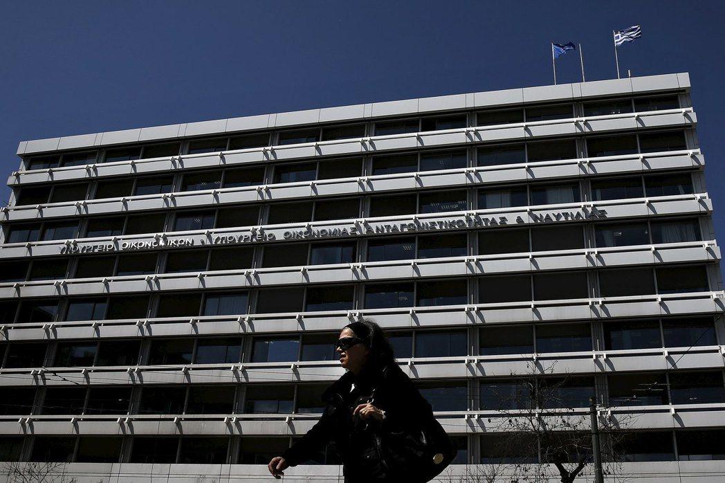 一名女子走過希臘財政部大樓。希臘過去幾年因債務問題被迫接受國際紓困,並厲行財政撙...