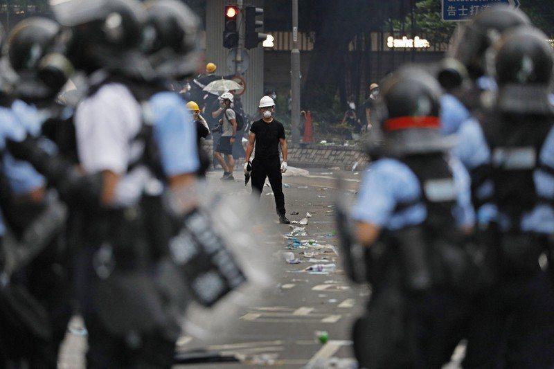 手持雨傘的香港民眾與警方。 圖/美聯社