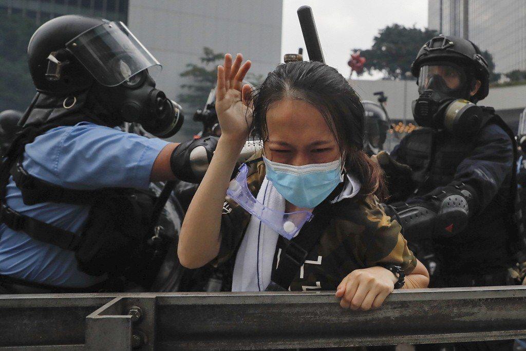 12日示威者遭港警無差別鎮壓。一名示威者遭港警武力壓制。 圖/美聯社