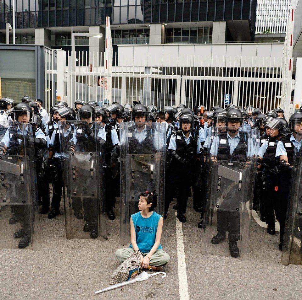 香港反送中遊行,林嘉露坐在鎮暴警察盾牌前抗議。取自Lam Lo臉書