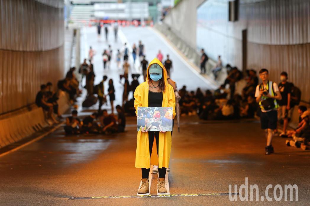 香港特首辦外圍,抗議群眾拿著遭港警毆傷的群眾照片佇立馬路中,要求林鄭撤回惡法。特...