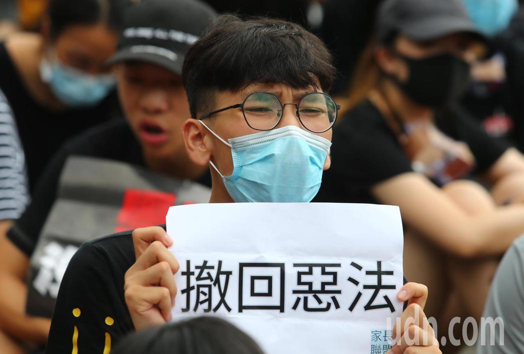 香港特首辦外圍,抗議群眾聚集,要求林鄭月娥出來對話,拿著抗議標語、高呼「撤回」口...