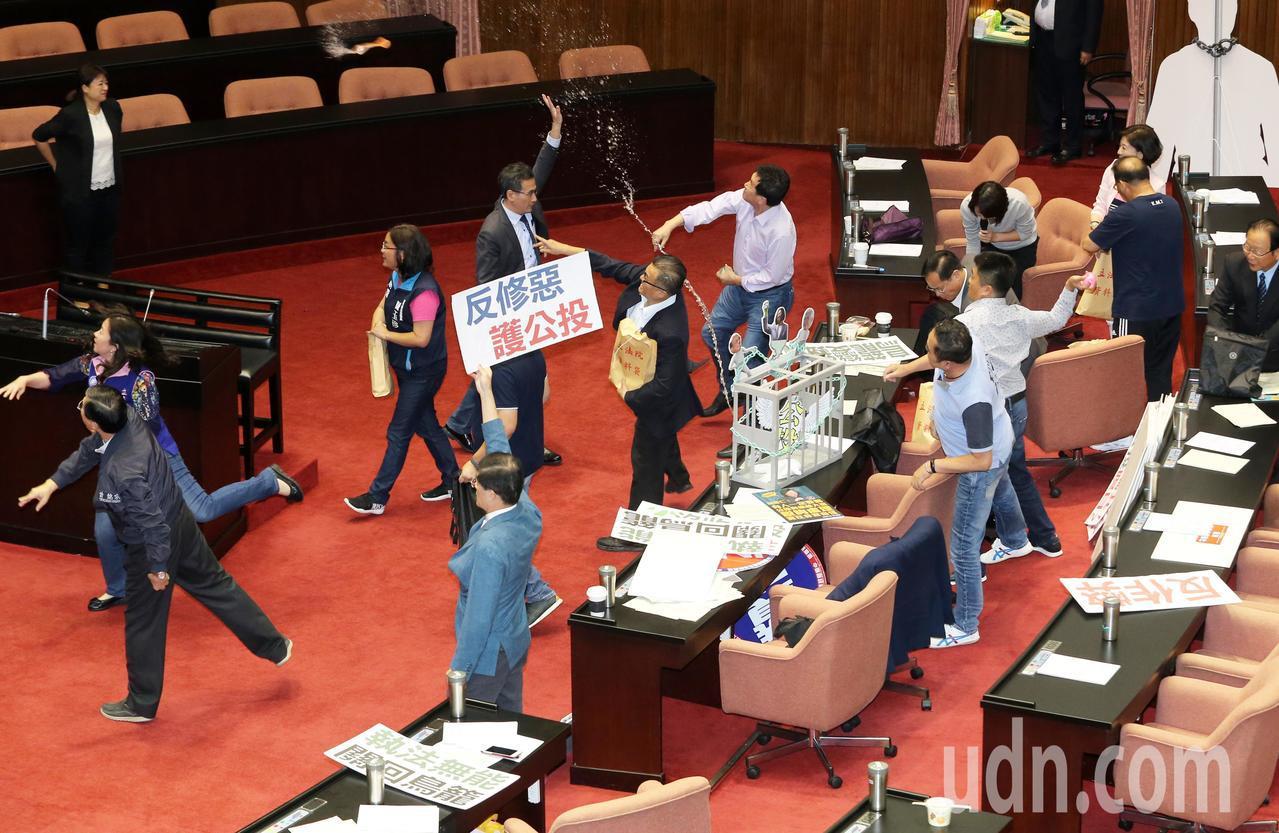 公投法修法三讀通過,國民黨團抗議這是「鐵籠公投」修法,朝主席台丟水球表示不滿。記...