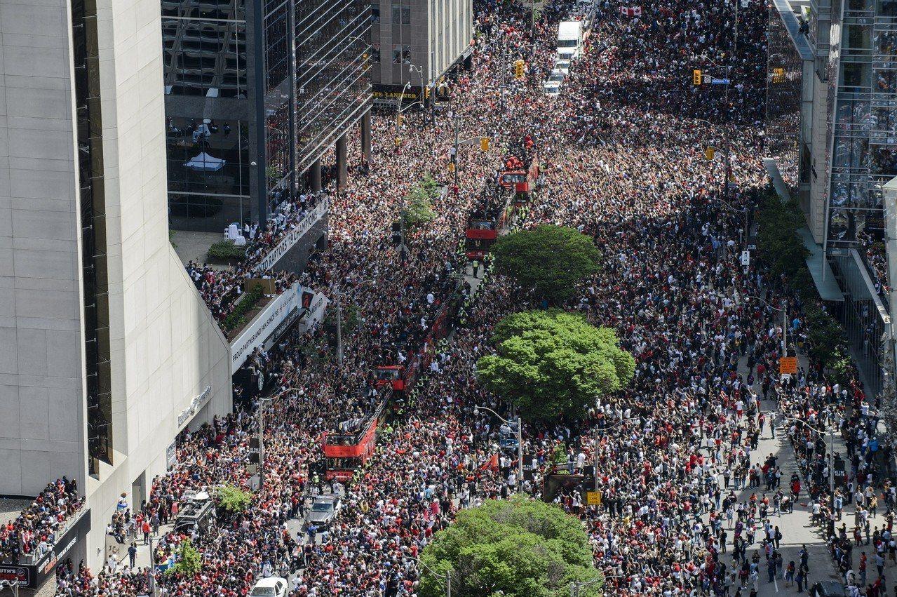 不少球迷翹班與翹課餐與暴龍遊行,多倫多市中心聚集球迷數預計約有150萬人。 美聯...