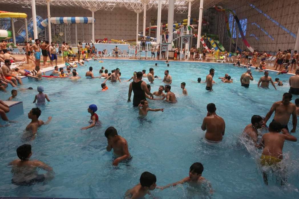 酷熱天氣使得許多伊拉克人擠在室內游泳池內泡水消暑。(法新社)