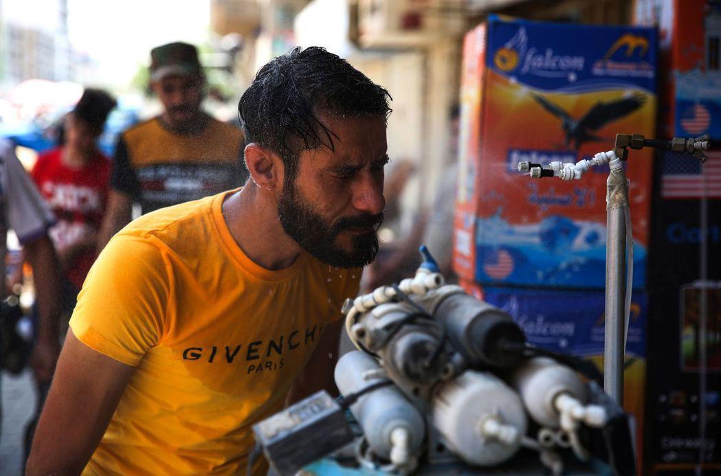 巴格達街頭常見到這種供人消暑解熱的水霧噴頭。(法新社)