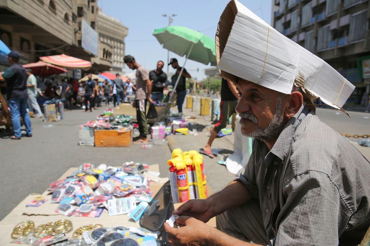 伊拉克街頭攤販帶起用紙板製成的簡便帽子來遮陽。(法新社)