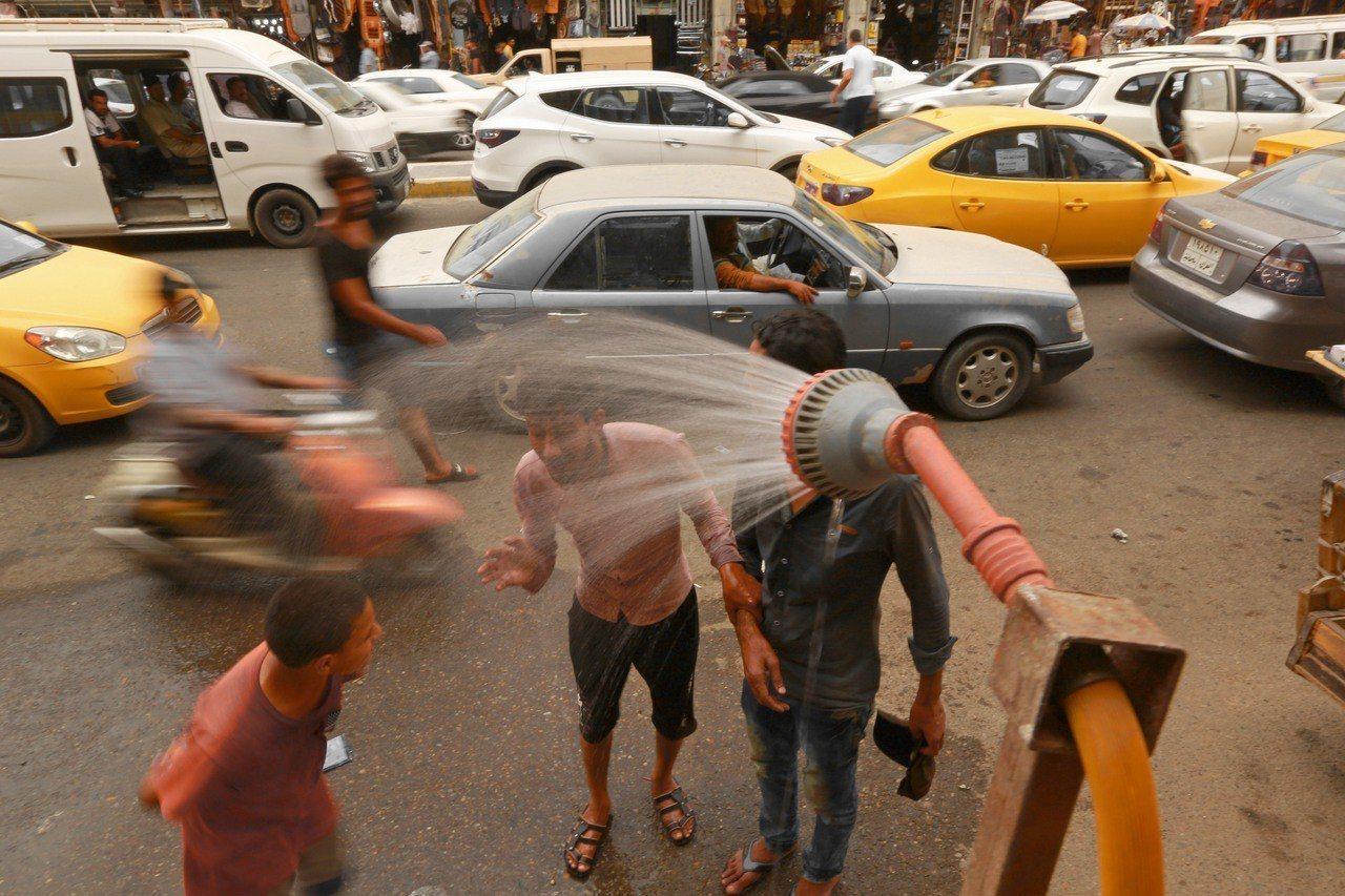 炎炎夏日,許多伊拉克民眾在在街邊沖水消暑。(美聯社)