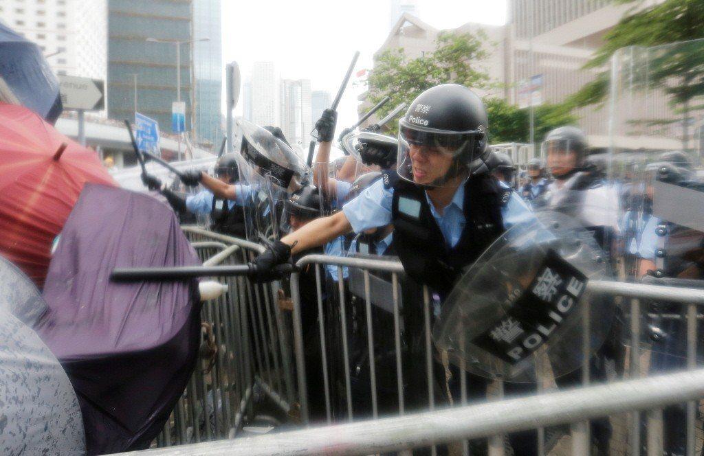 香港反送中遊行期間,港警持警棍武力驅離示威者。 圖/路透社