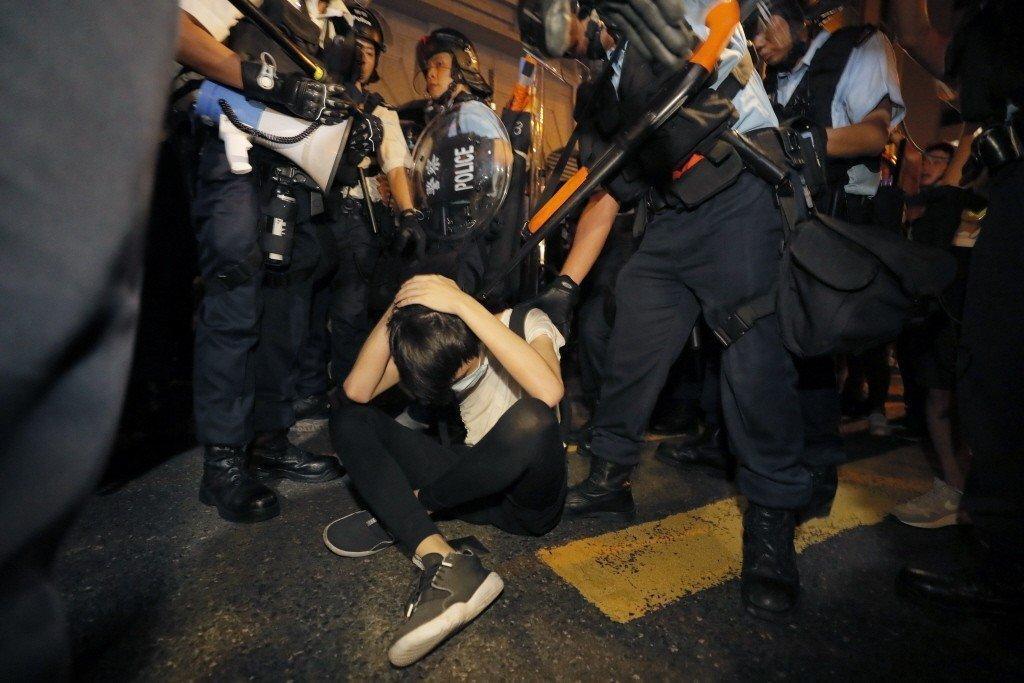 一名反送中示威者坐地以手保護頭部避免遭港警攻擊致傷。 圖/美聯社