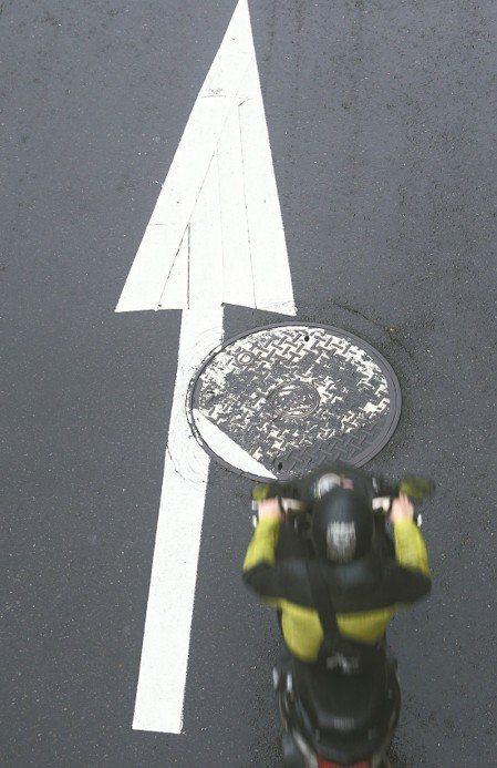 人手孔蓋每逢雨天就成為馬路地雷,容易害機車騎士自摔。本報資料照片