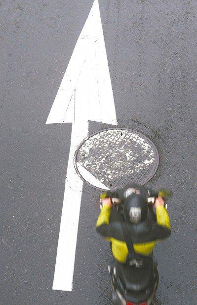 下雨天時,路上人孔蓋與標線往往成為機車騎士打滑摔車的「隱形殺手」。公路總局昨宣布...