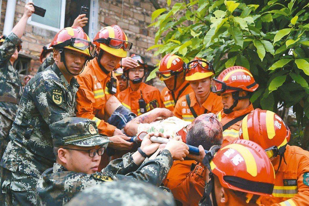四川省宜賓市長寧縣十七日深夜發生規模六強震,救難人員十八日從一棟受損大樓中抬出傷...
