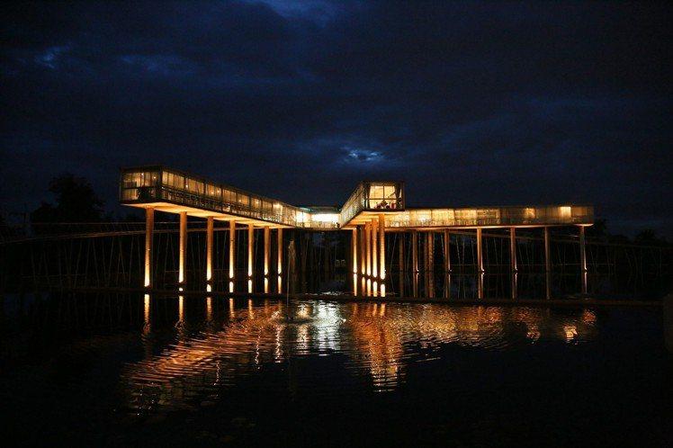 到了晚上,餐廳的燈光映照在水面上,就像是餐廳浮在水面上般,更有科技感。記者魏妤庭...
