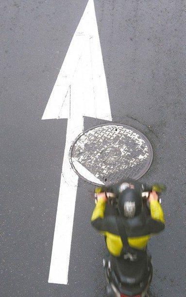 下雨天時,路上人孔蓋與標線往往成為機車騎士打滑摔車的「隱形殺手」。公路總局宣布新...