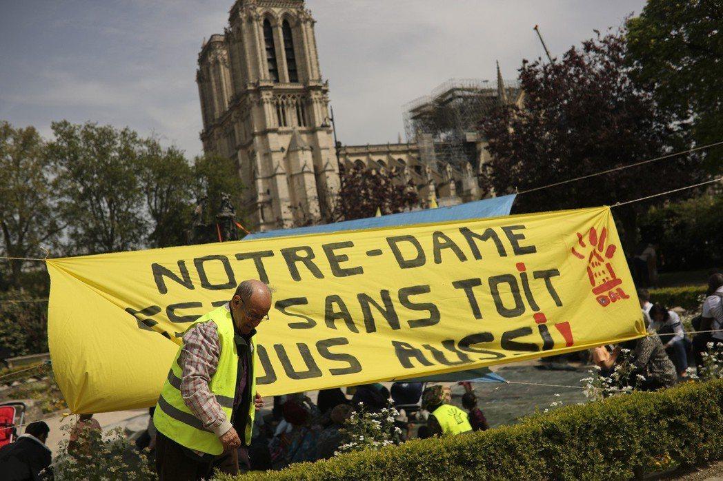 巴黎民眾對租屋亂象積怨已久,一名抗議男子在聖母院旁綁上標語「聖母院沒有屋頂,我們...