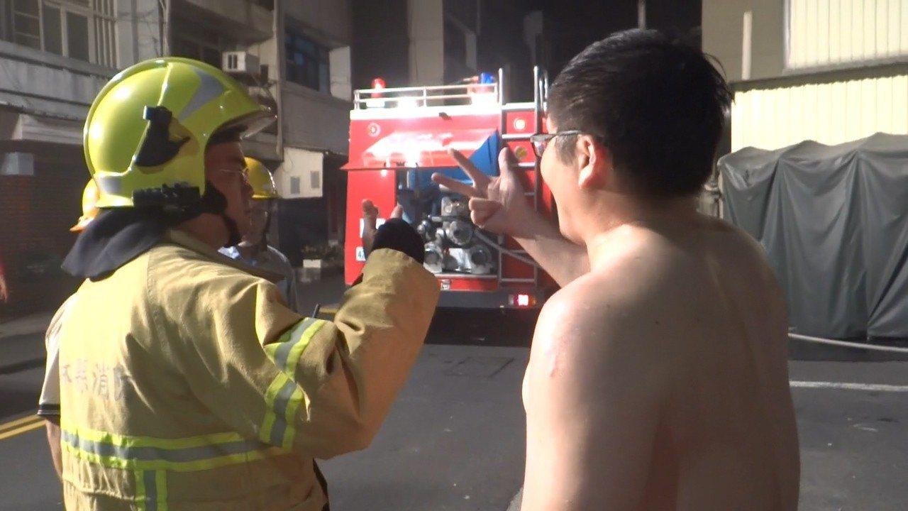 店老闆向消隊隊說火場只有他逃出來,還有6個家人受困其中。記者蔡維斌/攝影