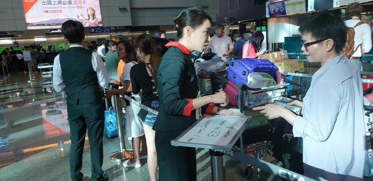 地勤人員先跟旅客確認被取消的班機,和說明作業程序。接記者鄭國樑/攝影