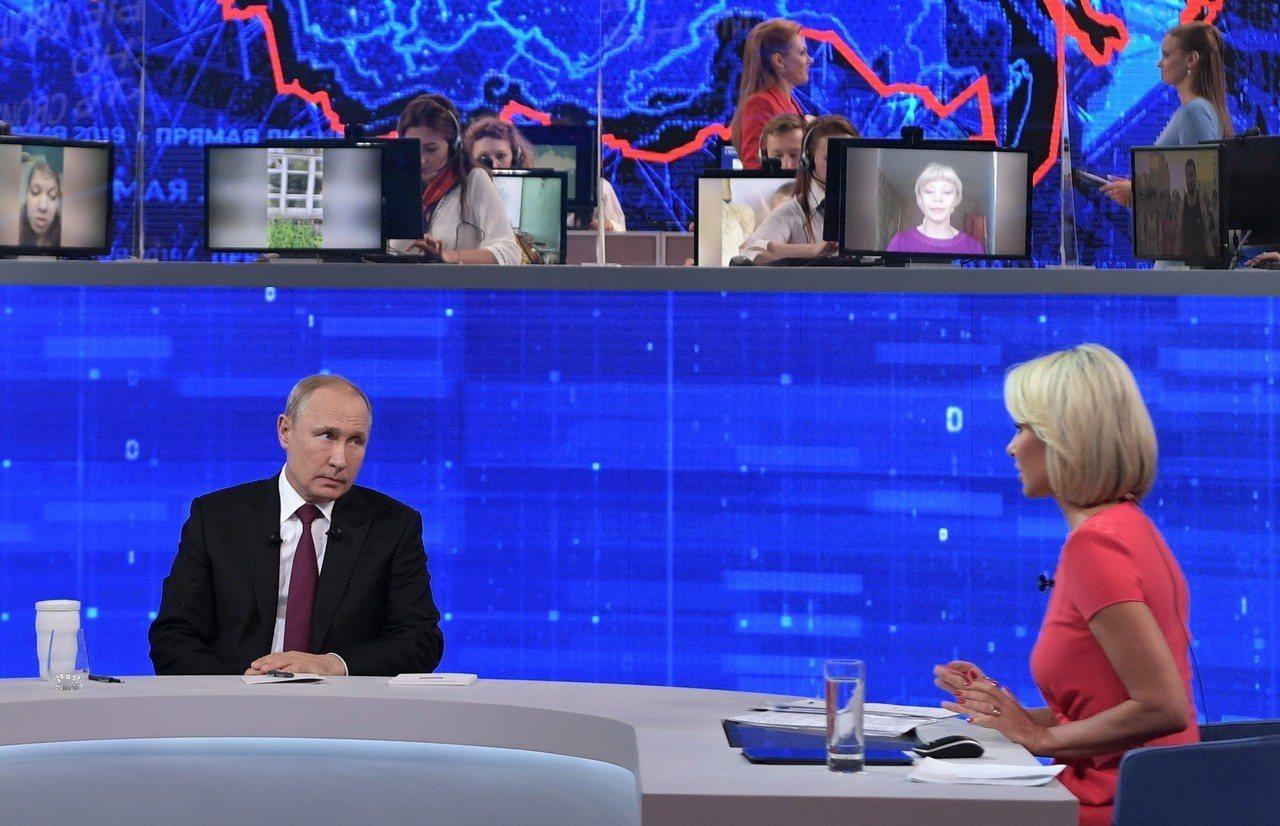俄國總統普亭(左)20日上電視接受全國民眾的提問。歐新社
