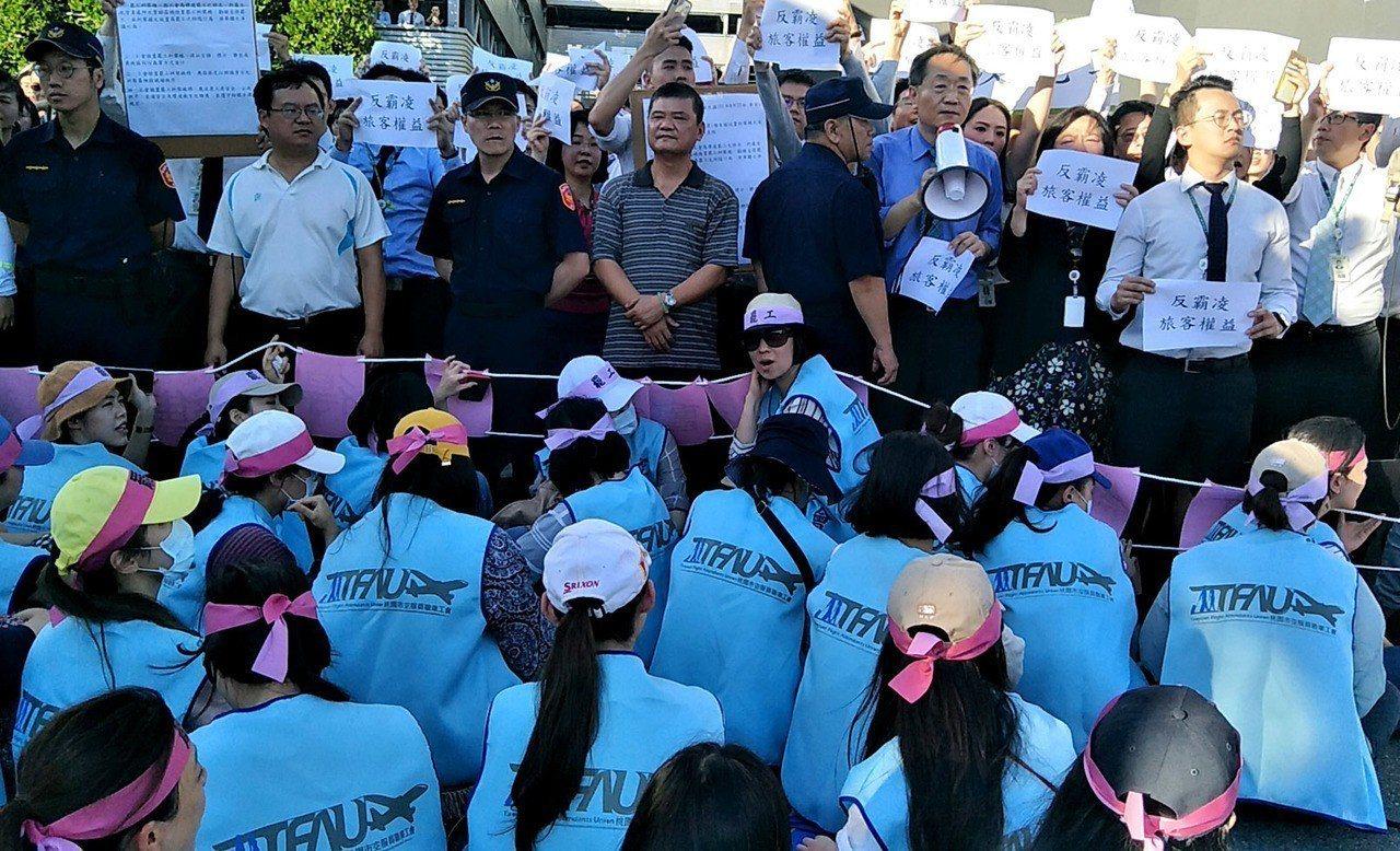長榮空服員在長榮航空大樓門口拉罷工糾察線罷工,與長榮航空反罷工員工互喊口號對峙。...