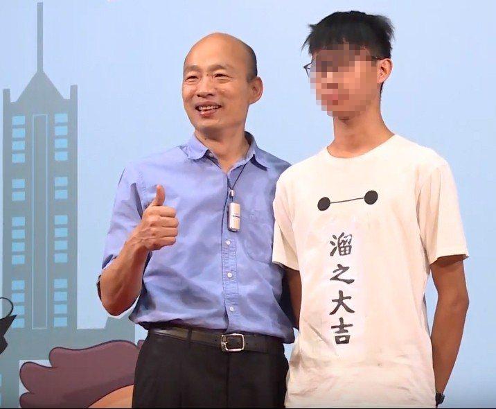 鳳山商工黃同學穿著自製的「溜之大吉」T恤,上台與市長韓國瑜合影。 圖擷自打馬悍將...