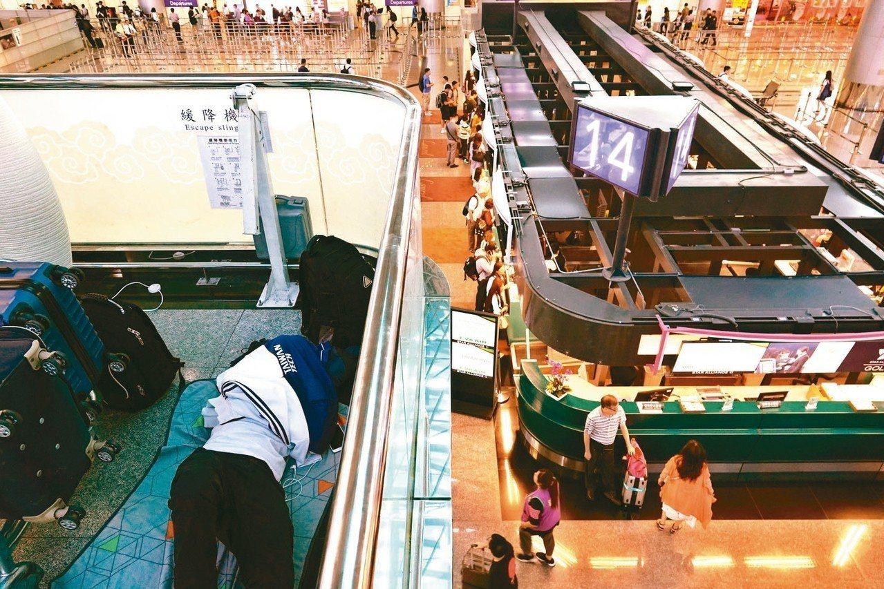 長榮空服罷工影響今天多個航班,一名等候的旅客躺在四樓的地板上補眠。 記者鄭超文...