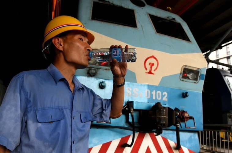 工人在高溫環境下工作,更需要補充水分。新華社