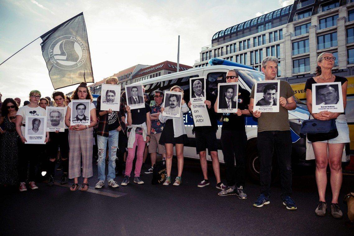 18日柏林的一場遊行上,民眾哀悼呂貝克之死,同時手舉近年遭受新納粹極右派組織暴力...