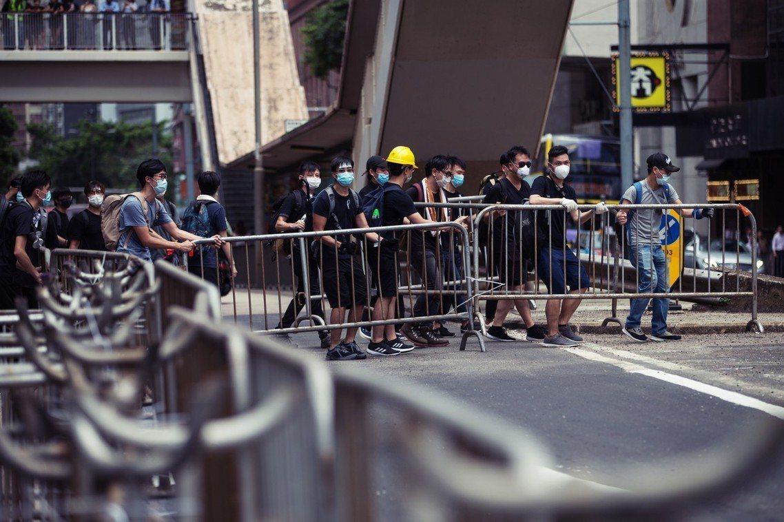 約在中午時分,位於灣仔軍器廠街的警察總部已被民眾團團包圍,示威者以鐵馬堵住警總正...