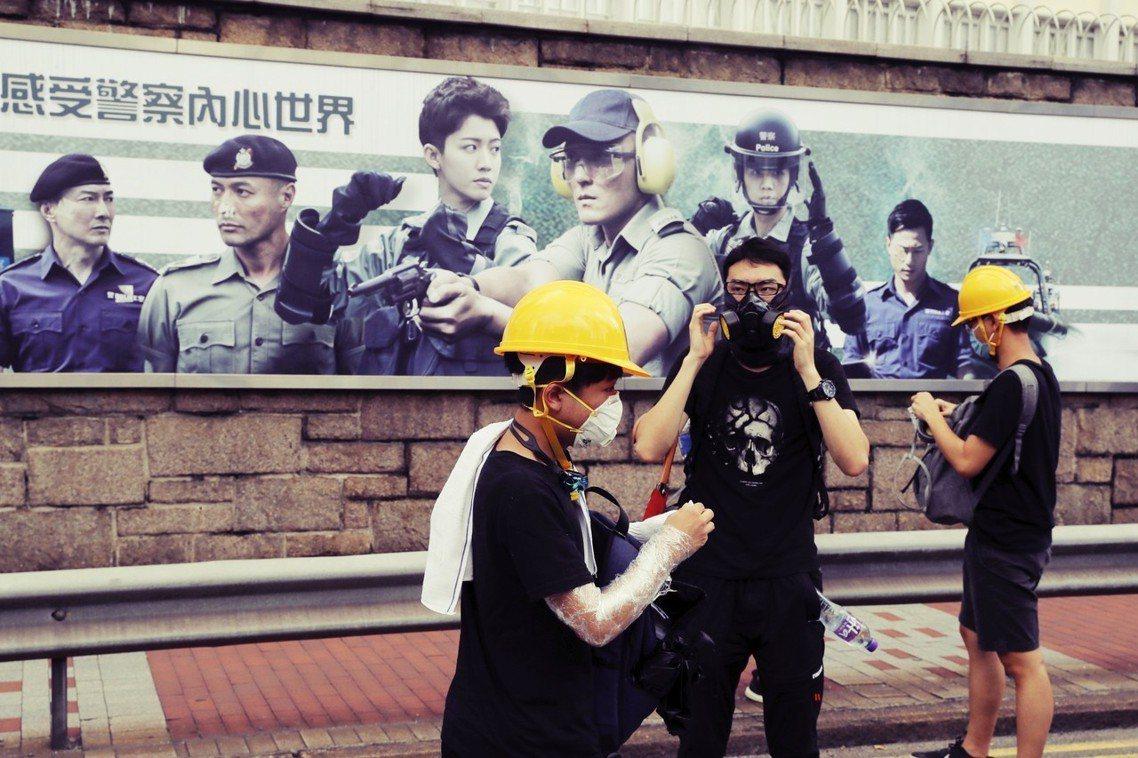 21日包圍警總的抗爭者,站在警總外一幅海報「感受警察內心世界」整裝,形成諷刺的對...