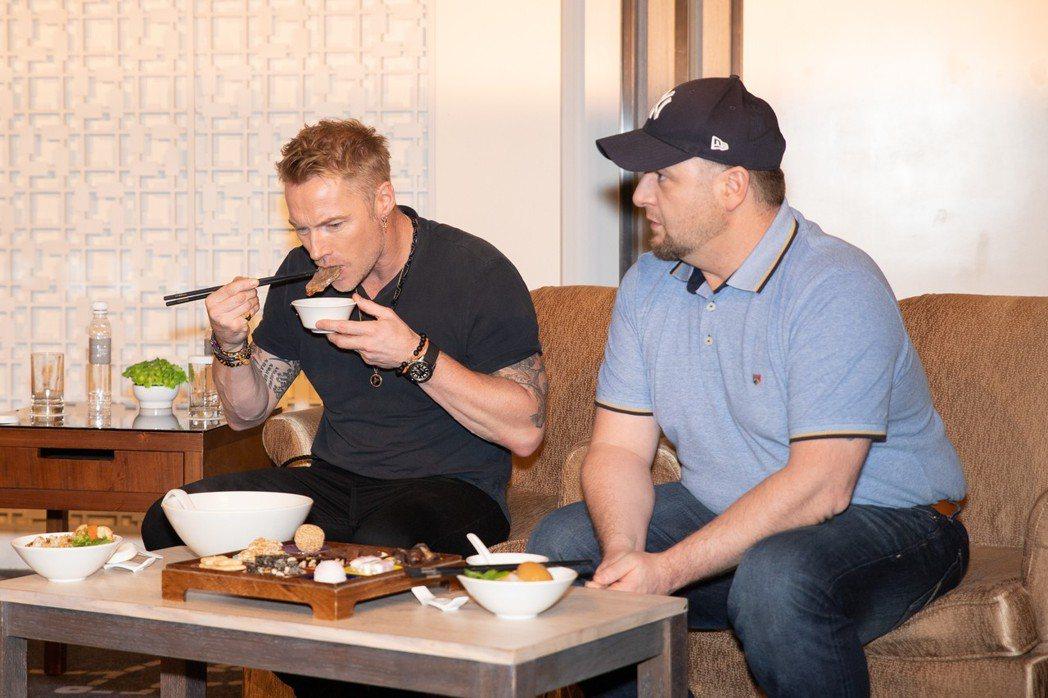 主唱羅南(左)及團員米奇(右)享受台灣美食。圖/傲世娛樂提供