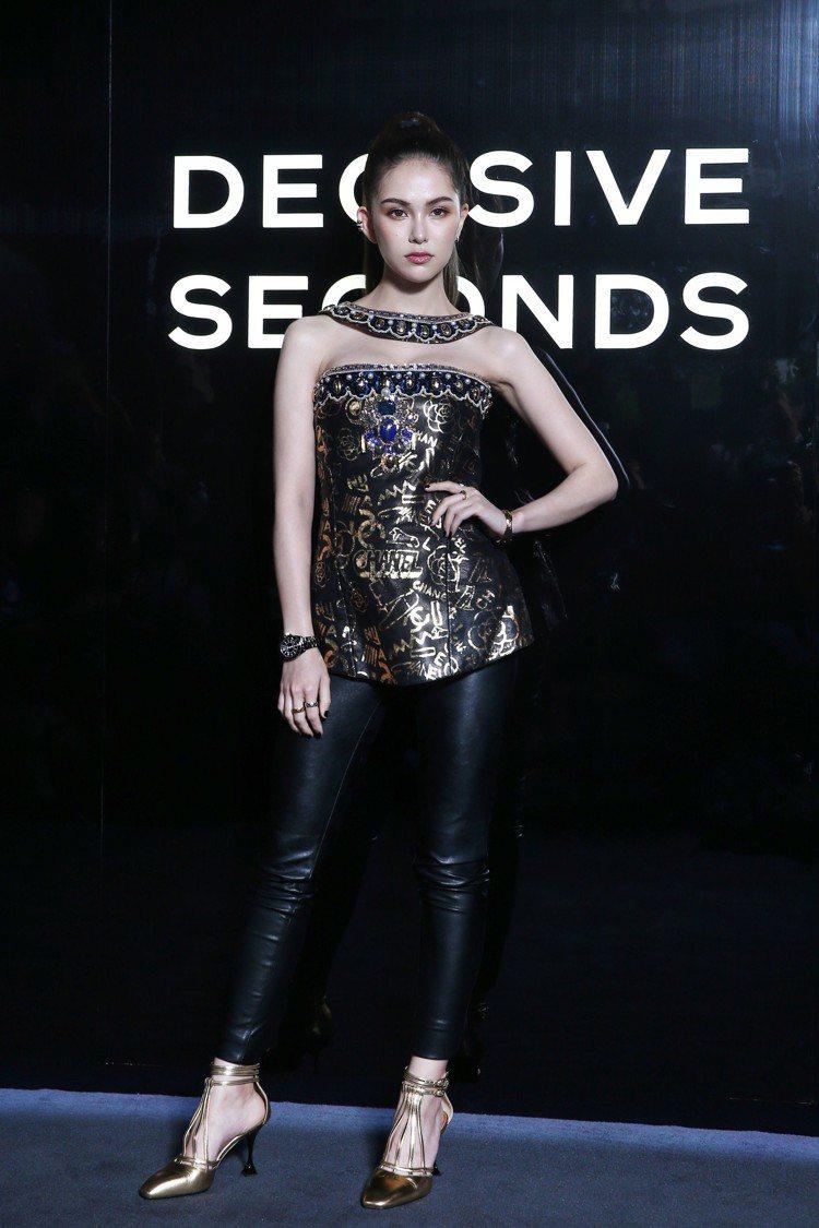 昆凌穿著香奈兒以埃及為靈感的巴黎-紐約工坊系列黑金圖案馬甲上衣,搭配黑色數字時標...