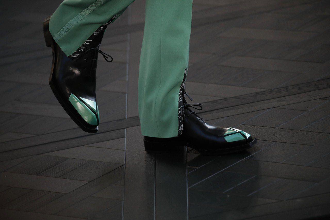長褲褲腳正前方開衩的小細節,讓腿顯得更修長。圖/美聯社