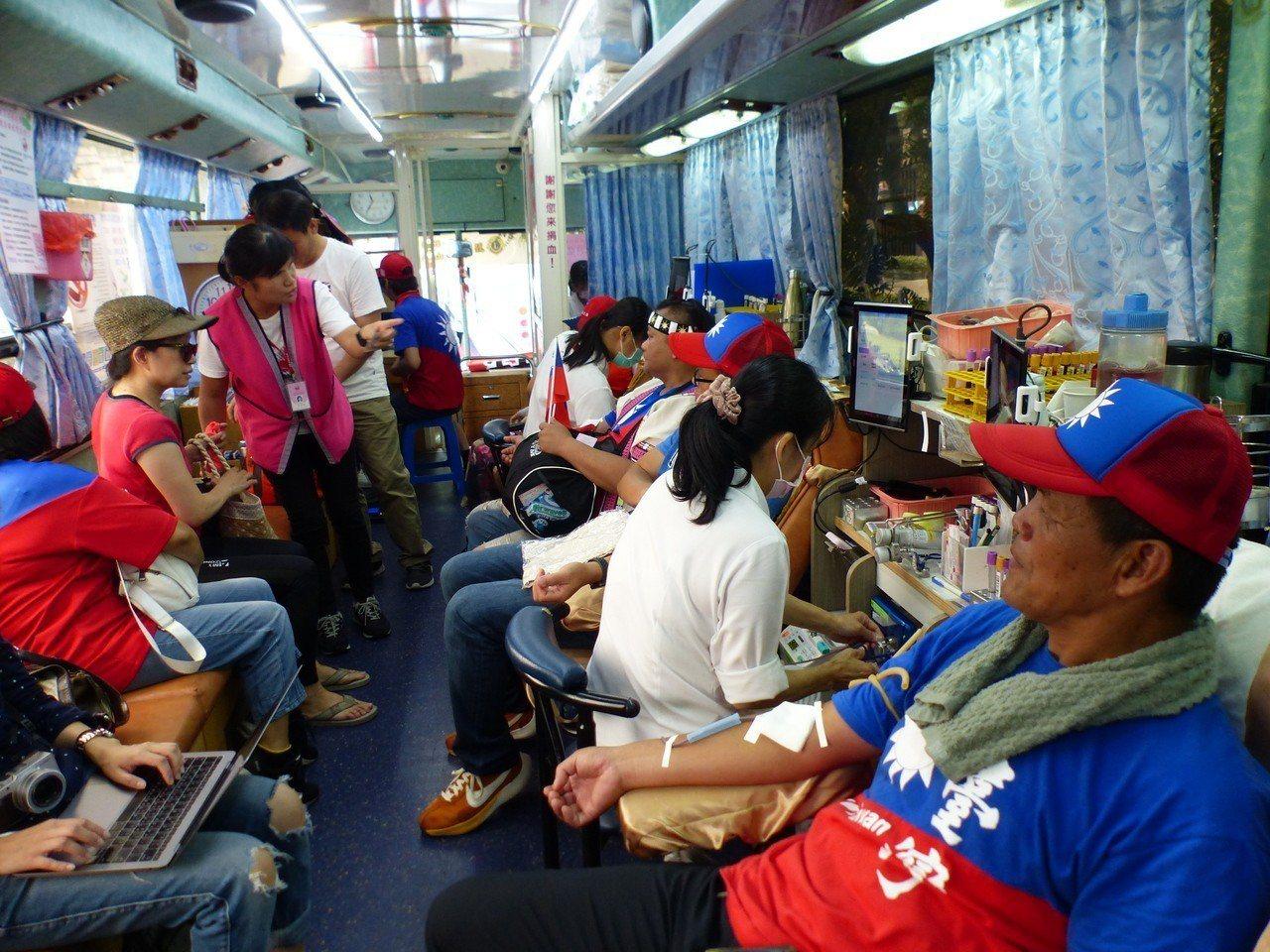 台中捐血中心今天在高雄市長韓國瑜台中造勢大會派駐2部捐血車募血,很多穿著國旗衣、...