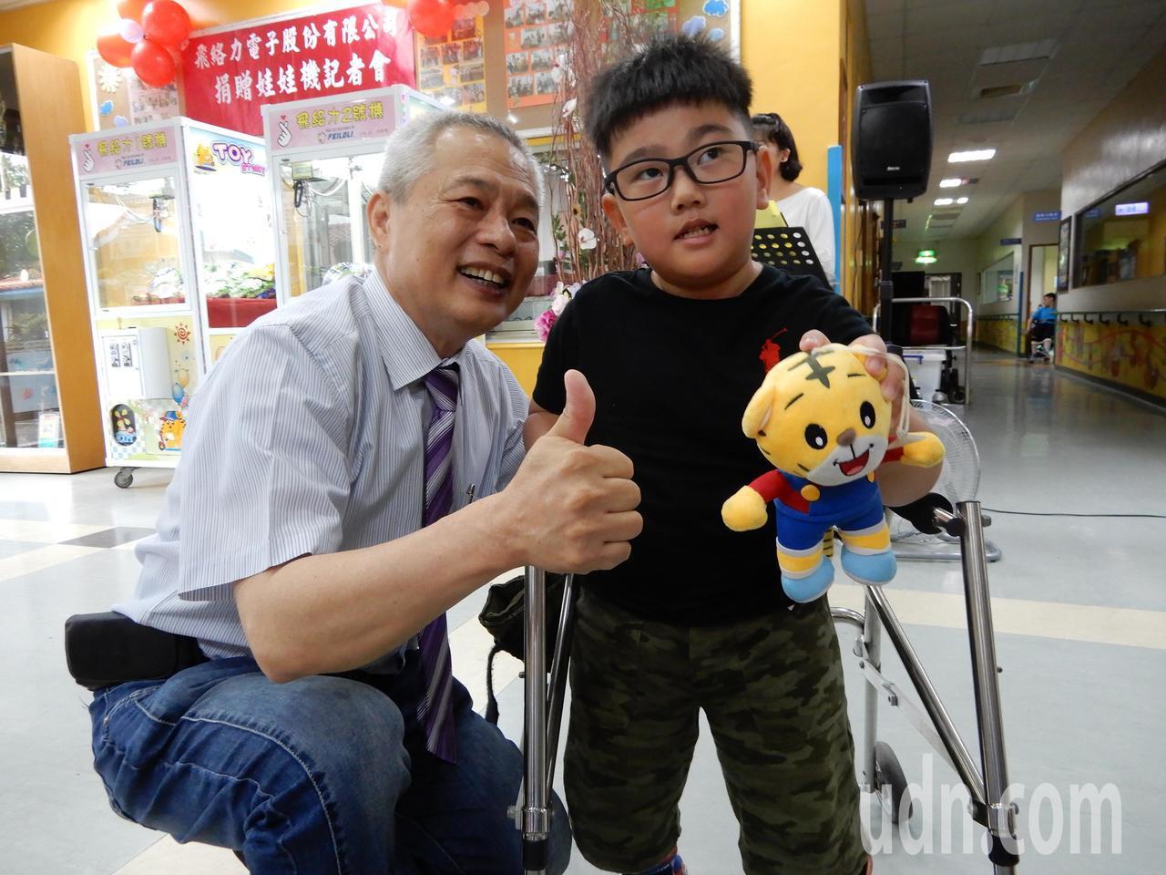 飛絡馬電子公司總經理楊奕強(左)鼓勵喜樂保育院孩子從夾娃娃機中學習手眼腦並用。記...