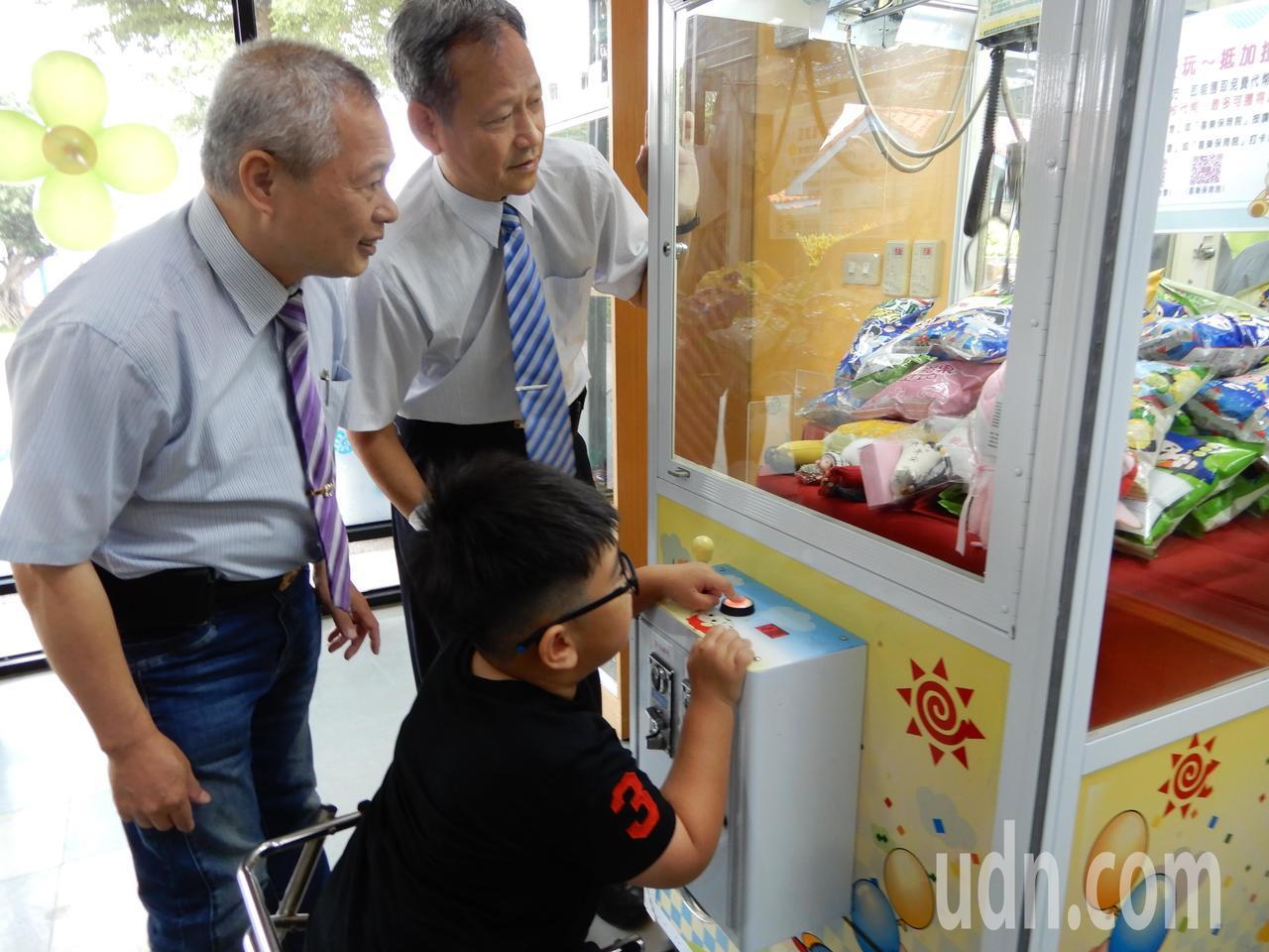飛絡力公司董事長蔡其明(右)、總經理楊奕強(左)陪伴喜樂保育院孩子玩夾娃娃機。記...