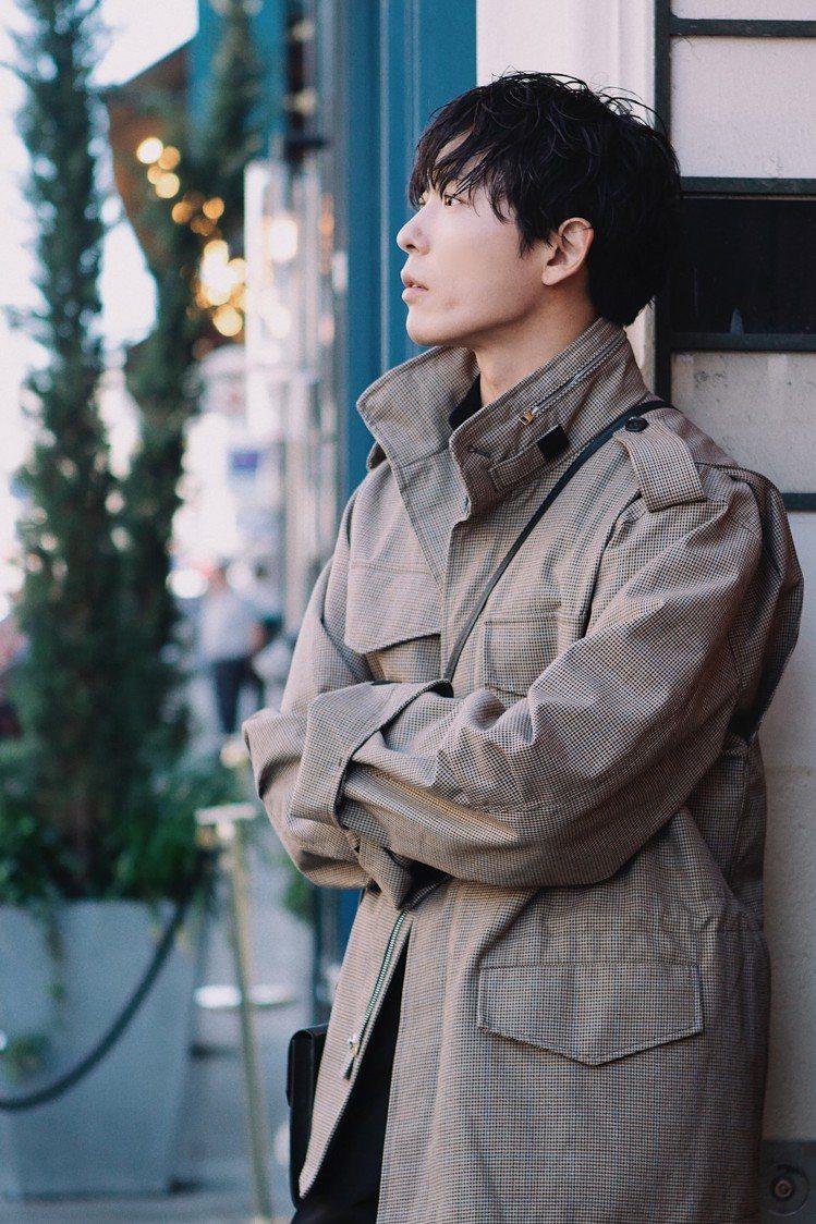 金材昱穿著dunhill千鳥格野戰夾克,內搭深藍色襯衫展現時髦的撞色效果,側背b...